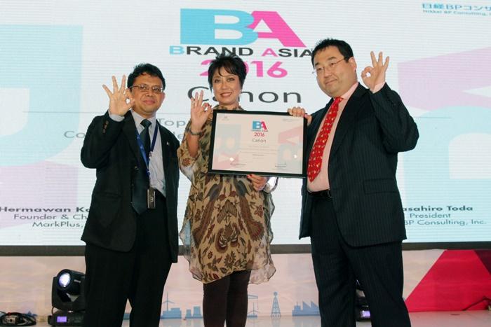 """Taufik –Deputy CEO Mark Plus Inc., Merry Harun – Canon Division Director pt. Datascrip dan Masahiro Toda –President Nikkei BP Consulting Inc. berfoto bersama pada saat penyerahan penghargaan Best Brand Asia 2016 di Jakarta, (17/5). Pada penghargaan tersebut Canon meraih penghargaan sebagai """"Top 3 Most Powerful Consumer Electronics Brand in Indonesia""""."""