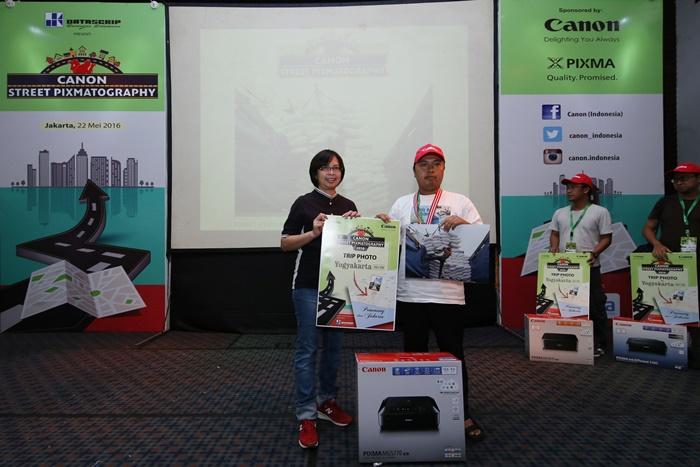 Monica Aryasetiawan – Division Manager Canon Consumer System Products Div., pt. Datascrip menyerahkan hadiah kepada Saiful Arif U.K., juara pertama Canon Street Pixmatography. Ia berhasil mendapatkan hadiah berupa Canon PIXMA MG5770 dan tiket perjalan wisata foto ke Yogyakarta.